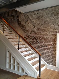 exposed brick walls and a crisp, clean staircase. Love the way the stairs are trimmed out, and the wire bannister keeps the focus on the wall.