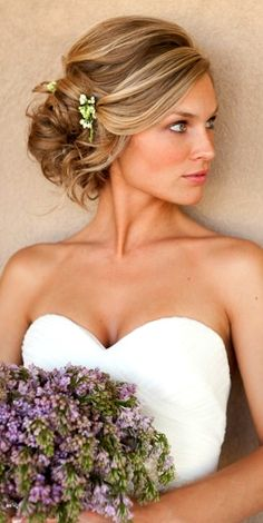 Bride's low loose bun side part wedding hairstyle with flowers