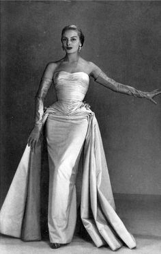 1952 Model in white satin evening gown, bodice is finely gathered, narrow skirt has two side panels that is detachable, by Jean Dessès