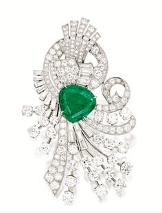 EMERALD AND DIAMOND BROOCH, RAYMOND YARD   Centring on a modified pear-shaped emerald weighing 5.75 carats, to a stylised background of ribbon design, set with brilliant-cut and baguette diamonds together weighing approximately 9.00 carats, mounted in platinum, signed Yard.