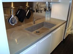 Oversized concrete countertops including an integrally cast kitchen farm sink with drainage ramps and linear sink detail for Manhattan apartment. This kitchen was featured in the New York Times (please see Press weblinks)