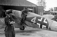 A Luftwaffe ground crewman services the cockpit of a Messerschmitt Bf-109, via Jedem das Seine. It's likely that the pilot is looking on at the left.