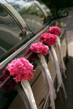 Pretty pink pomanders decorate the bridal car.