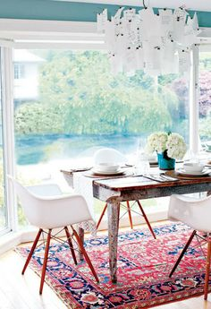 #Eameschairs and a colorful rug bring a surprising twist to this dining area with a poolside view