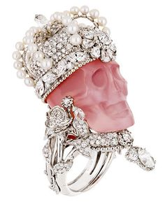 , looks like white gold, diamonds, and pearls, enhancing a carved rose quartz skull.