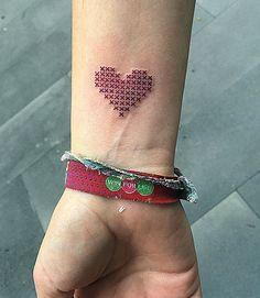 Petit tatouage discret sur le poignet d'un coeur en broderie