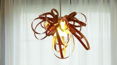 Casey make a sculptural chandelier from a pendant light and wood banding. From the experts at HGTV.com.