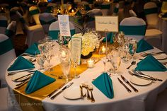 Details for a teal and gold wedding reception tablescape.  Use teal napkins, a gold table runner with white tablecloths and white spandex chair covers so the colors are more accents then main feature.