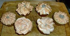 white cupcakes with orange buttercream frosting flowers