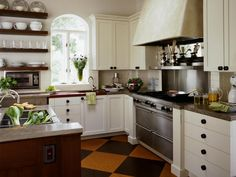 This country-style kitchen features 10-foot ceilings, limestone countertops and a food prep surface made of African bubinga wood. The Venetian plaster range hood, cabinetry and floating shelves evoke an English cottage look.