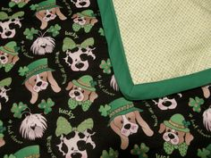 """Hand Tied 39 X 41 Mini Quilt-Let Your Inner by CatsOnTheGreen Let your Irish shine with this hand tied quilt measuring 39 inches by 41 inches. Several breads of dogs wearing green hats and bows with gold specks. The statements """"Wearing of the Green"""", """"4 Leaf Cover"""" and """"Lucky"""" are interspersed among these lovely pooches too."""