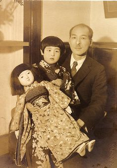 young Japanese girl in kimono carrying Ichimatsu doll, with her father