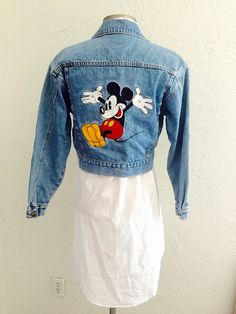 An 80s cropped denim jacket with hand embroidered hearts, mouse ears, and a dancing Mickey on the back Bust:38 Length from shoulder to bottom hem:16