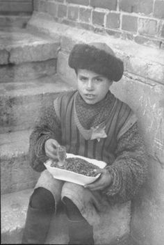 """A young boy selling sunflower seeds. """"The boy in the fur hat was called """"Aldona"""". I remember him because he always used to sing a Lithuanian love song called 'Aldona'. His parents had perished in the beginning of the war and he lived with his aunt."""" George Kadish photo."""