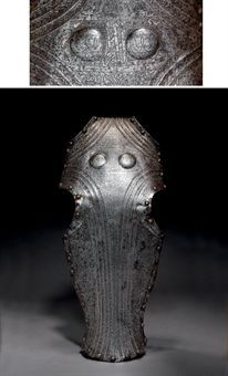 A MAMLUK CHAMFRON  EGYPT, SECOND HALF 15TH CENTURY  Formed of a single piece of steel shaped at the eyes and with a narrow flange at the ears, the forehead with two convex roundels, a series of fluted bands edging the ears and eyes and running together down the length of the nose forming an elongated lozenge, the flutes decorated with a series of chevrons or zig-zagging ovoids, the lozenge finely engraved with elegant arabesques terminating in palmettes and issuing lotuses...  24 1/8in. long