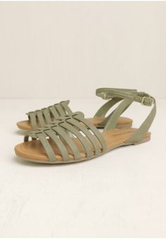 Crafted in olive-hued faux leather, these flat sandals feature a strappy woven front design with adjustable ankle straps.