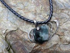 Surový nefritový kámen zasazený v cínovém rámečku. Kámen je velký 3/3 cm, celý šperk je 6,5 cm široký a 4,5 cm vysoký, Je zavěšený na silné šňůře se zapínáním na magnet.