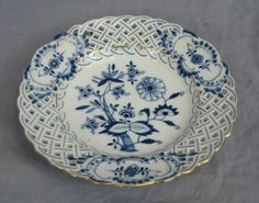 Meissen blue onion reticulated plate with gold trim.
