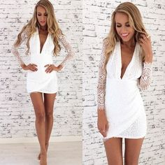 Deep plunge neckline on a white romper with lace sleeves