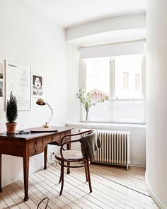 Contemporary minimalist interior with antique desk, Thonet chair, and industrial lightning