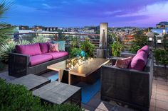 aménagement terrasse moderne - salon de jardin en rotin, coussins pourpres, table basse en bois et plantes vertes