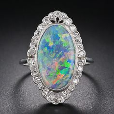 An entrancing elongated oval black opal displaying a full color palette: green, blue, yellow. orange and red, is elegantly presented in an Edwardian era platinum and diamond mounting - circa 1910. The delicately hand crafted scalloped frame glitters with tiny round diamonds supported by a lovely scroll work gallery.