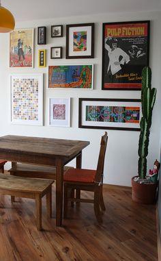 Mesa de madeira de demolição, parede cheia de quadros e cacto