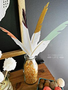 Painted feathers and a vase filled with kernels makes an easy decoration on any table. #thanksgiving