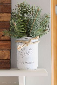 Use a distressed-white Mason jar, bits of evergreen, and some rope to add visual interest to a kitchen shelf.