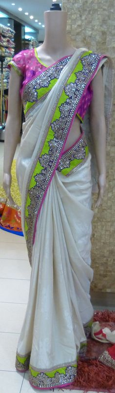 Cream Handloom silk with self print saree with a heavy Kundan border in lime green and purple and a designer blouse in pink and purple jute silk brocade and a silk lime green border with gold thread work plus a extra blouse piece. Exclusive to Apna's £429