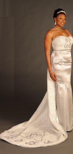 This eyecatching ethnic full length sleeveless and strapless fitted evening or bridal gown has jacquard fabric on the top of dress with Sankofa symbol in the front. Fabric below the waist of the dress is made of crepe satin. Detachable train is made of jacquard fabric and lined with silver lame fabric and has exquisite silver lace trim all around edge of train. The train also has the Sankofa symbol meaning Return to your past, and the Gye Nyame symbol representing the omnipotence of God…