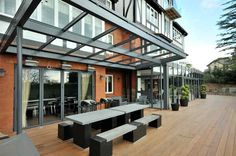"""As you can see from these photo's ultra modern can fit very snuggly alongside older more traditional designed homes. Heritage Projects are very adept at working with glass and steel (balustrades, glazed boxes and balconies) we have found that more and more home owners are looking for powder coated aluminium structures which includes bi fold doors, all which create the ultimate """"wow"""" factor to your home."""