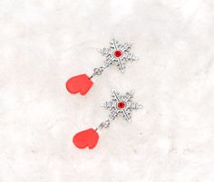 La Zapada! - A sweet snowflake pair of earrings, with the base made out of silver metal (shaped like a snowflake with a red glass crystal inserted in the middle) and mittens charm, handcrafted out of red and white polymer clay. They are perfect for the holiday season, a stylish accessory for the wintery days!    Click image to find more cool handmade jewelry by me! #HolidaySeason #earrings #ChristmasIsComing