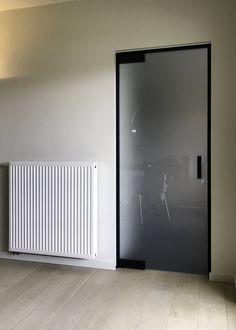 Mat glazen deur met zwarte scharnieren en minimalistische omlijsting die een perfecte afsluiting garandeert. De deur kan in beide richtingen openen