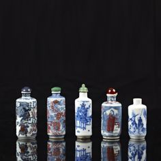 Ensemble de cinq flacons tabatières de forme tronconique en porcelaine bleu, blanc et rouge à décor de scènes des trois royaumes et d'objets mobiliers. Deux marques Yongzheng apocryphes.