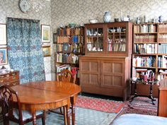 The Sitting Room of The Emery Walker House with cabinet designed by Philip Webb, original 'Apple' wallpaper by Morris & Co and carpet from William Morris's bedroom at near by Kelmscott House.