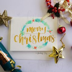 """Christmas card featuring """"Merry Christmas"""" in gold ink and a hand-painted green Christmas wreath."""