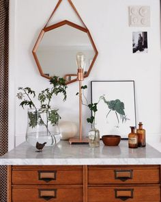 This cute little console looks like a mini modern day apothecary. And we love it so much for that. For more inspiring decor ideas, follow this board. #curiographer #console #entryway