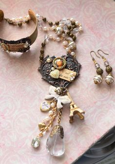 Renee Hong FUF 10/10/14 Parure; Mona Lisa, C'est la vie charms, crystal, locket, Eiffel Tower, and more! Matching necklace, cuff bracelet, and earrings.