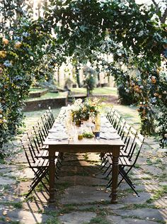 Long wood table. Dinner setting. Cafe chairs. Wedding reception.