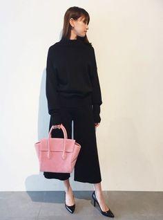 ニットセットアップに映えるバッグをポイントに。  ブラックのニットセットアップに映えるピンクのバッグを合わせてポイントに。