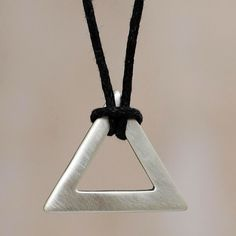 Jose Antonio Ibeibarriaga transforms a perfect triangle of sterling silver into a captivating pendant. Crafted with a brushed satin finish, the pendant is worn on black cotton for a masculine necklace of minimalist artistry.