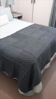 Knitted DROPS blanket with squares in different structured