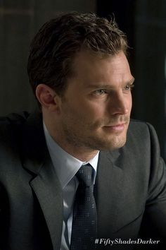 """Christian glances down at me, his gray eyes un- readable. Oh, he just looks glorious—tousled hair, white shirt, dark suit."" - Anastasia Steele 
