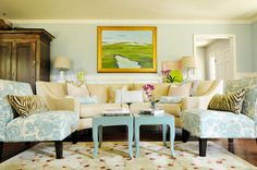 The mood of this room.... white trim, light teal wall, wood cabinet, printed fabric, landscape arwork