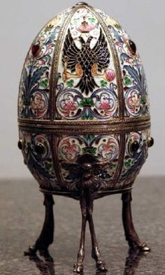 """Of this egg we don't know either the name or the year of creation.This egg is made of heavy, emerald green glass, decorated with enamel flowers and leaf motives in different colors, as well as the two-headed Imperial eagle. The egg rests on a metal base, standing on three pairs of legs fashioned like deer legs and hoofs. On the bottom of the glass the word """"Fabergé"""" is etched, together with the numbers """"0025"""". This egg is now kept in a private collection."""