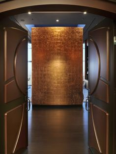"""""""Minimalist design 1. Choose high-quality and beautiful material, then let it stand on its own. In this entryway, the wall is simply stunning in its own right. The gold leaf wall treatment glows with warmth. No need for art"""""""