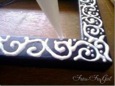 Decorate an old plain frame with glue, let it dry, then paint over it so it looks like carved wood.