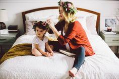 Madre peinando a su hija con flores en la cabeza