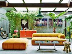Sofa e Pufe amarelos em living com plantas
